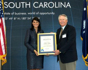 Cleve Nichols of US Fibers, accepts the Ambassador award on behalf of Edward S. Oh, with Gov. Haley.