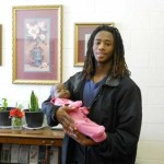 De Vasha Blacks holding baby in parenting education; March's nontraditional student.