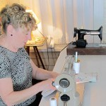 "Here Jo Ann is using her ""best friends"" in her artwork, her 1954 Singer 301 Sewing Machine.  She has recently bought the earlier Singer electric (on the table) that, after a trip to the sewing machine expert for a cleaning, will be put to use also.  Jo Ann's hairdo is so complimentary to the work she does, and to her home, which salutes the era of the 40s and 50s in particular."