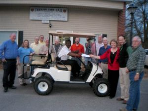The Trenton Community Development Association presented the Trenton Council with a check for their portion of a donation that made possible the purchase of the golf cart in which Chief Of Police Deke Tanks is seated.  Kevin Corey from U.S. Fibers, another donor toward the purchase, joined Council and TCDA members in posing with the Town's new golf cart.