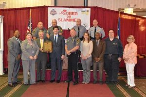 SCDPS Director Leroy Smith and SCDOT Acting Secretary Christy Hall present the award to Senator Shane Massey and Representative Bill Hixson, joined by other Edgefield County officials.