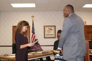 Jennifer Sumner administers the oath of office to Lamaz Robinson, Johnston's new Chief of Police.