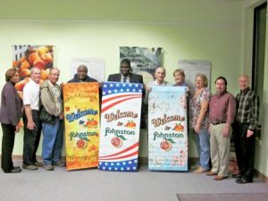 Johnston Mayor Terrence Culbreath (Center, holding banner) accepts the Johnston Development Corporation's (JDC) donation of three banners for the downtown area. Members of the JDC Board are, from left, Goldie Dean, Tommy Stone, Chris Clancy, Noah Peterson, (Culbreath), Roger Lamb, Bridget Clark, Debra Aston, Frank Davis and Dean Campbell. Also on the JDC Board are Mary Anne Hair, Andy Livingston, Shane Massey, Don Smoak, John Timmerman and Ann Yonce.