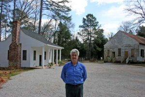 The new resident caretaker, Barney Lamar, standing before Horn's Creek Church and the new caretaker's cottage.