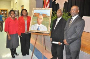Speakers and Board members at the W.E. Parker event gather around the portrait following the unveiling: L. to R., Sally Cooks, former board member; Latoya Hammond, speaker and board member; Willie Campbell, board member and gave the benediction; and James Bibbs, speaker and board member.