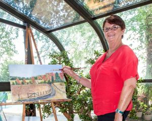 Debbie Black in her glassed-in studio makes a few changes to a painting of the driveway to her rural house.