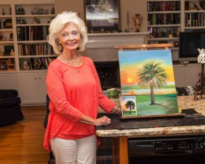 Virginia Culbertson shows off a painting in progress, a palmetto tree based on a photograph taken by friend Pamela A. Cook, a member of Chicks That Flick.