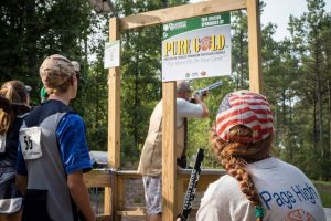 Youth look on as their fellow competitor takes aim at a sporting clays station.