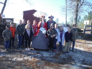 A group of home schooled children stand with Justin and Tonya Guy in period dress at the entrance to the Battle of Aiken. Pictured are left to right: Grant Rauton, Wyatt Roberson, Whit Miller, Makena Rauton, Jackson Graham, Bennett Graham, Haviland Graham, Tonya and Justin Guy, Asher Ireland, Ella Mathis Miller, Gracie Roberson, Whittaker Graham, and Knox Rauton.
