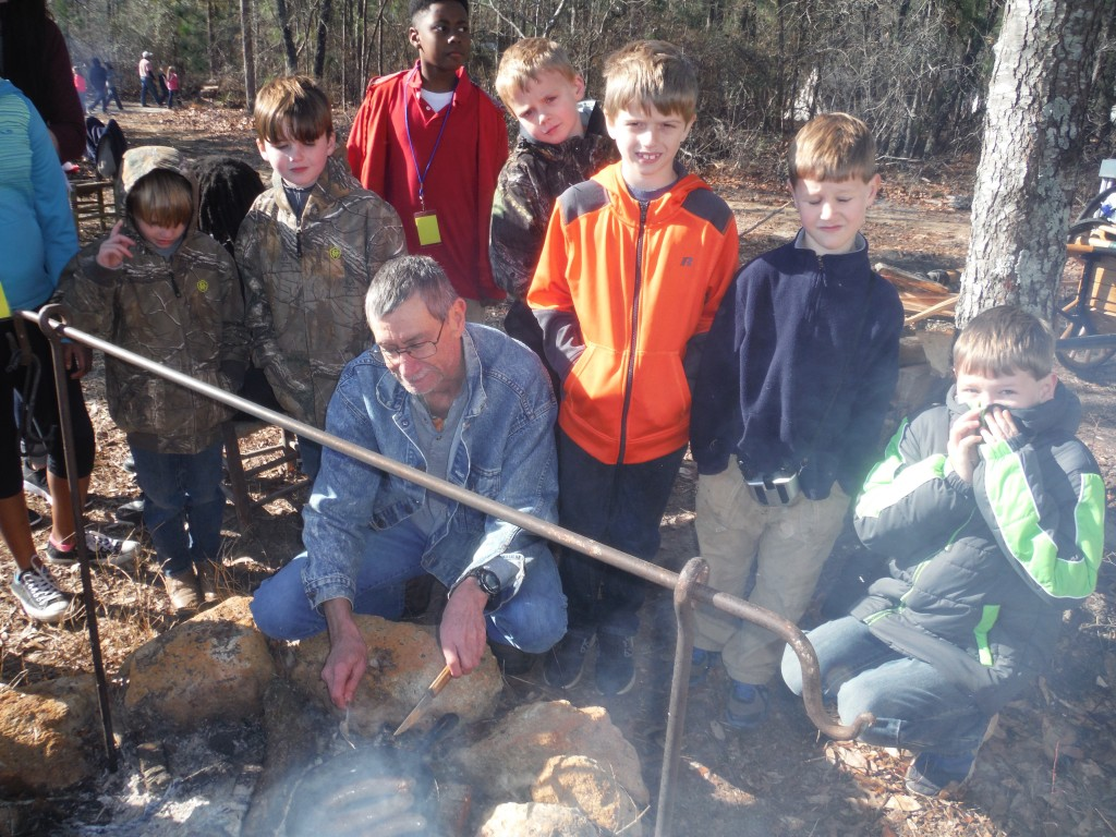 Keith Sexton surrounded by area home schooled students as he roasts sausage on an open fire at the Battle of Aiken.